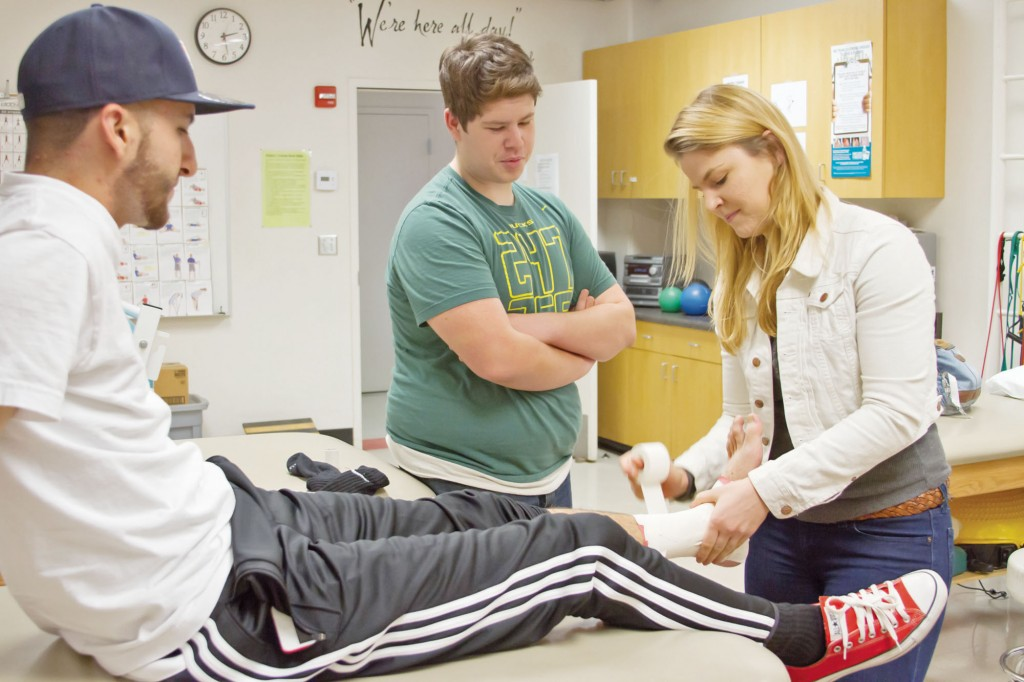 Natalie Livermore 20, tapes Hector Gonzalez's  ankle. The students are members of the Sport Medicine Internship offered at Pierce College, in Woodland Hills, Calif. on Dec. 4, 2014. photo by Erick Ceron.
