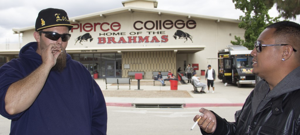 """Pierce College students Drew """"Big Sexy"""" Stern, 27, and Brian Humpay, 27, smokes a cigarette with a tar filter  in the faculty and staff parking lot in front of the South Gym on Thursday, May 5, 2016 in Woodland Hills, Calif. (Photo by: Alan Castro)"""