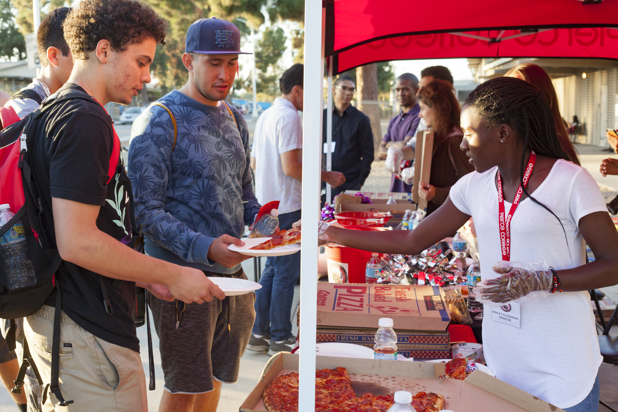 Ashely Alexander, ASO agriculture department senator, serves pizza to Joel Pagan and Jose Morfin at the ASO Volleyball Tailagate outside Pierce's South Gym on October 12, 2016 in Woodland Hills, California. Photo by Calvin B. Alagot / Roundup