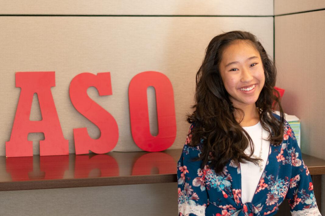 Vivian Yee stands in front of ASO sign